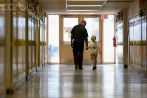 Teacher and elementary student walking down school hallway
